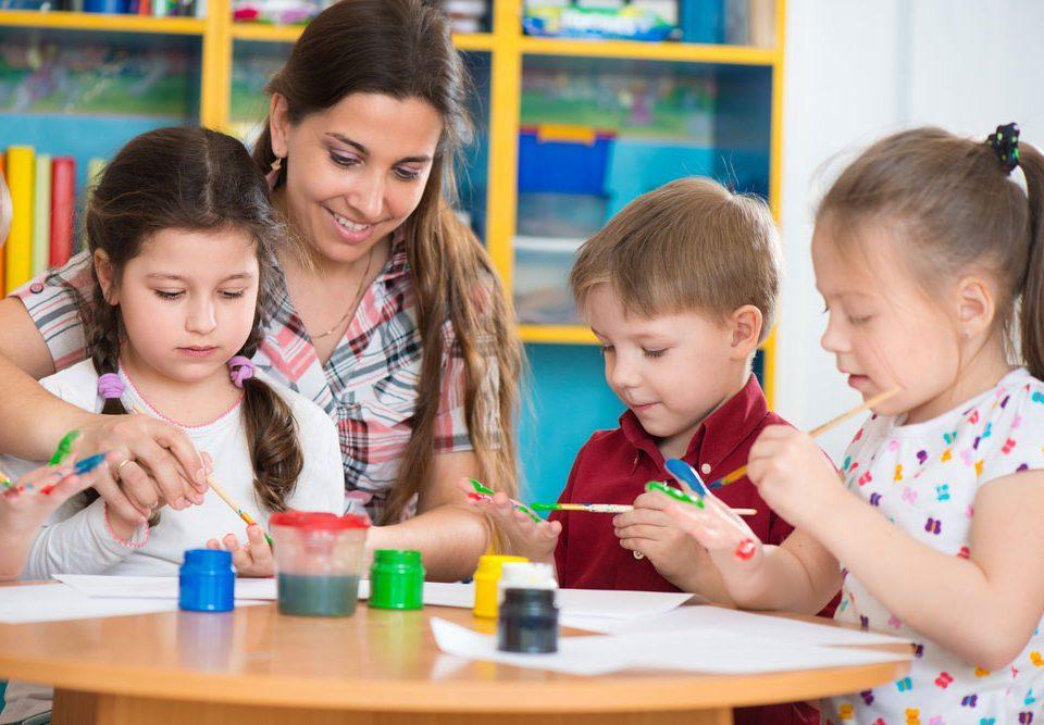 teacher helping children paint