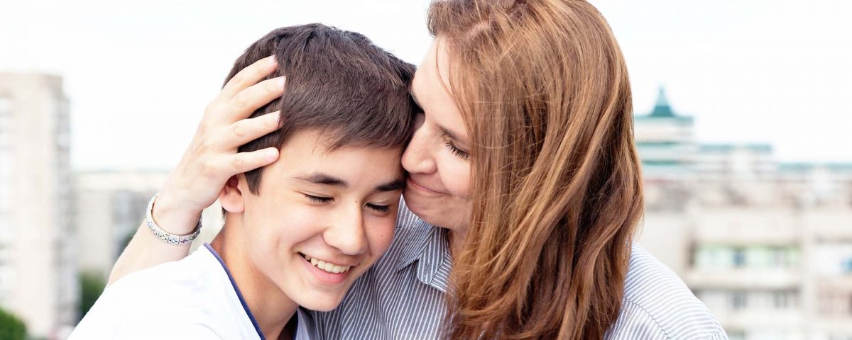 mother smiling and hugging her son