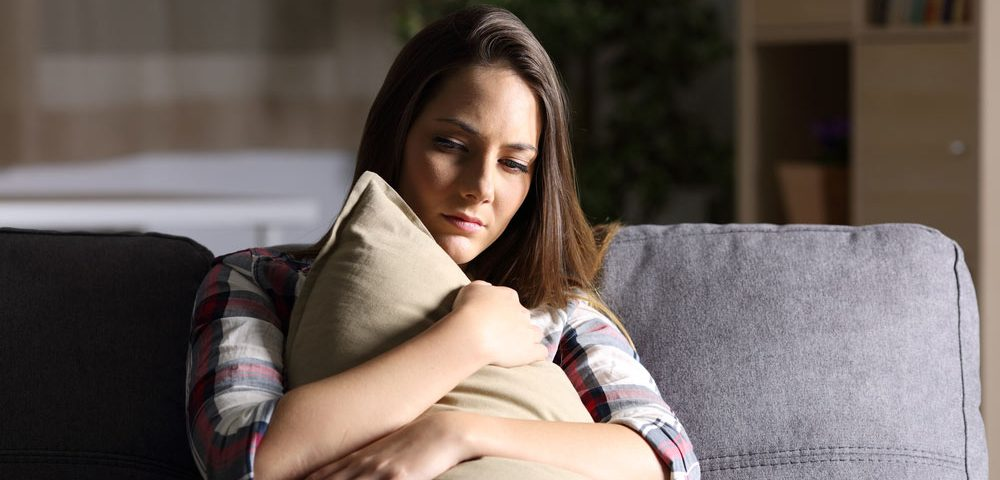 girl with anxiety holding pillow